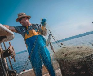fisherman on boat with net